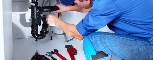 Plumber performing repairs to plumbing